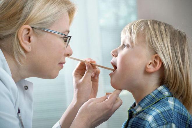 Врач смотрит горло ребенка