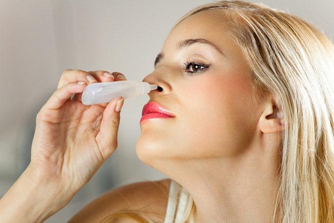 Женщина закапывает нос