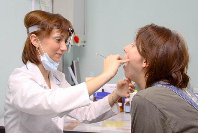 Доктор исследует горло женщины