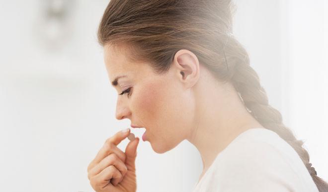 Девушка глотает таблетку от горла