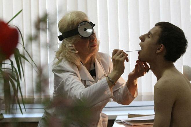 Отоларинголог производит осмотр горла